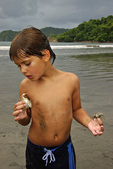 Royce plays with crabs at tideline, Manuel Antonio National Park, Costa Rica