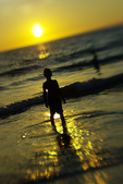 Boy watching sunset at Hapuna Beach, South Kohala, Big Island, Hawaii