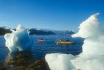 Kayaking by beached bergy bits, off Growler Island, near Columbia Glacier, Prince William Sound, Alaska
