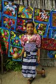 A Kuna Indian girl dances before her display of molas, San Blas, Panama