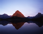 Grinnell Peak lit by sunrise light, reflected in Swiftcurrent Lake, Many Glacier area, Glacier National Park, Montana