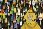 lobster buoys and a smiling caricature of a lobsterman, a roadside sight in Maine