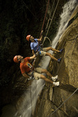 Friends rappel by a waterfall in the rain forest south of Puerto Vallarta, Mexico