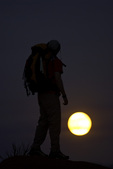 A backpacker hikes in the light of a full moon, on the Tonto Trail below Horseshoe Mesa, Grand Canyon National Park, Arizona
