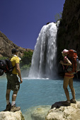 Backpackers pause to drink in the beauty of Havasu Falls, Havasupai Reservation, Grand Canyon
