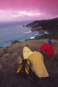 A hiker watches sunset from his camp at Ryan's Den, Great Ocean Walk, Victoria, Australia