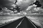 Summer clouds flow over a rural highway in northern Arizona