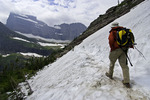 Hiking across a snowbank on the Grinnell Glacier Trail, Glacier National Park, Montana