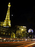Traffic streams along the Strip at night, beside the Paris Casino and the Eiffel Tower, Las Vegas, Nevada