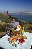 Summer picnic with Dungeness crab, sourdough bread, strawberries, and California wines on the Marin Headlands, with a view of the Golden Gate Bridge and San Francisco, California