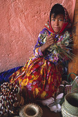 A Tarahumara girl weaves a basket for tourists at El Divisadero, on the edge of Copper Canyon, Mexico