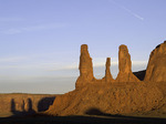 A spring sunrise casts shadows of the Three Sisters, Monument Valley, Arizona