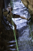 Rappelling down a waterfall chute in Benson Creek canyon, north of Cedar City, Utah
