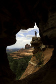 Adventurous hiker viewed through a keyhole arch, off Schnebly Hill Road, Sedona, Arizona