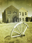 Wagon wheel and buildings in the summer sun, Bodie State Historic Park, California