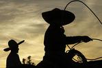 Mexican cowboy roping ay sunset, at Rancho Ochoa, Laveen, Arizona