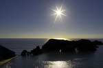 Setting sun behind sea arches on the Mendocino County Coast, northern California