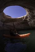 Kayaking below the sky window double arch in Rock Creek Bay, Lake Powell, Utah