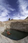 Kayaking in a slickrock waterhole below Cookie Jar Butte, Padre Bay, Lake Powell, Utah