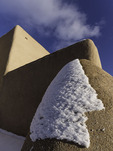 Christmas snow clings to the adobe of the Church of St. Francis of Asis, Ranchos de Taos, New Mexico