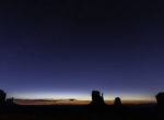 Stars sparkle above the Mittens predawn, Monument Valley, Arizona