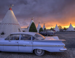 A summer sunset lights up the teepees of the Wigwam Motel, and the vintage cars, on Old Route 66 in Holbrook, Arizona