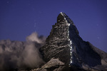 Stars track and clouds swirl over the Matterhorn, lit by the moon and bearing lights celebrating the 150th anniversary of the first ascent in 1865, shot from the Berghaus Fluhalp, Zermatt, Switzerland