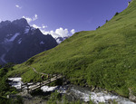 Hikers cross a bridge east of Mont Blanc, northwest of Courmayeur, Italy