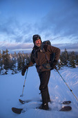 Nature guide Robert Fluet skis to a summit for sunset in Monts Valin NP, Saguenay-Lac-Saint-Jean, Quebec, Canada