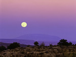 Full moon setting at sunset into the penumbra above Navajo Mountain, from Hunts Mesa, Arizona