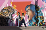 Girlfriends walk past murals in downtown El Paso, Texas