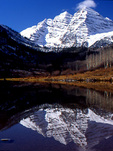 Light snow on Maroon Bells with reflection in Maroon Lake, Colorado