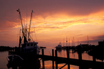 """Sunset over the waterfront at Ocracoke Village on Ocracoke Island. The lagoon pictured here is known as Silver Lake and is called """"The Creek"""" by the locals. The island is part of North Carolina's Outer Banks and except for the village is completely within Cape Hatteras National Seashore. It is located along the Outer Banks Scenic Byway."""