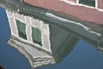 Reflections of buildings in the canal. Burano, Italy, a colorful town located in the Venice Lagoon about an hour by boat from Venice, Italy.