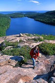 Maine, Acadia National Park, Hiker on Bubble Rock above Jordan Pond