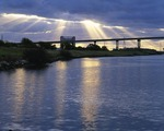 Texas, Freeport, Old Brazos River channel and bridge with sun rays