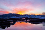 Maine, Stonington, town and harbor area with snow at sunset, low tide