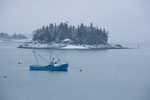 Maine, Lubec, fishing boat and island in harbor with snow and storm