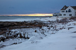 Maine, York Beach, Cape Neddick (Nubble Head), home on rocky shore in record snow storm/blizzard of February 2013, breaking storm at sunset
