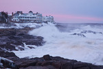 Maine, York Beach, Cape Neddick (Nubble Head), breaking waves below buildings on rocky shore in record snow storm/blizzard of February 2013, sunset in breaking storm