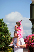 Father raises daughter in princess costume to watch parade on his shoulders! Walt Disney created a magical world with his characters of fantasy. The daily parade at Disney World, Orlando Florida is an exciting moment for kids and adults alike, as they encounter characters whom they've only imagined. The realistic portrayal, music, costuming and performance by the actors/players enhances the crowds' enjoyment!