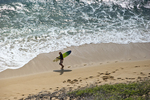 Surfer carrying his board along the sand at Kuilei Cliffs Beach, a popular surfing spot that is east of Diamond Head.