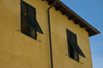 Lucca, pair of dark green shutters on an ochre house. Lucca is in Tuscany, in northern central Italy.  The city is known for