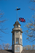 Cupola with the British flag at the Capitol at Colonial Williamsburg.  Colonial Williamsburg's 301-acre Historic Area includes 88 original 18th-century structures, many of which are open to the public.  It is a town-size museum, exhibiting 18th-century Williamsburg as it was on the eve of the Revolution. At that time Williamsburg was the capital of the Colony of Virginia.  Exhibition sites, costumed historic interpreters and demonstrations of colonial crafts and trade bring the 1770s back to life.