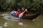 Lisa Paciulli, Masma and Riana paddling a sampong downstream from Betumonga Research Station to Betumonga Village