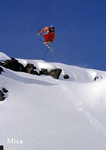 Skier flying off cliff.