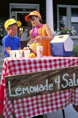 Children prepare and sell lemonade in front of their home as young entrepreneurs finding customers.