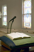 Church Pulpit with microphone, bible, pews and stained glass, Brooklin, Maine, USA