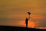 Silhouette of a child flying a kite.