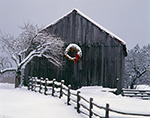 Lit Holiday Wreath on Barn after Heavy Snowstorm